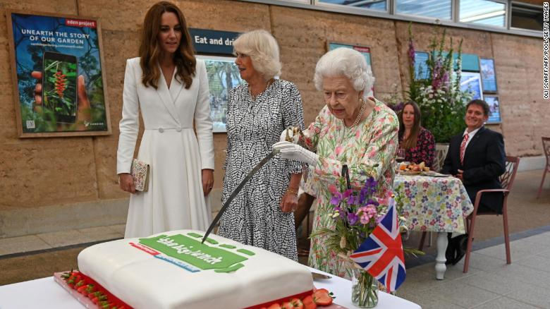 Her majesty, the Queen cutting a cake with a ceremonial sword.